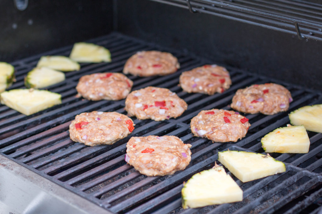 Picture of raw turkey burgers and pineapple on a grill