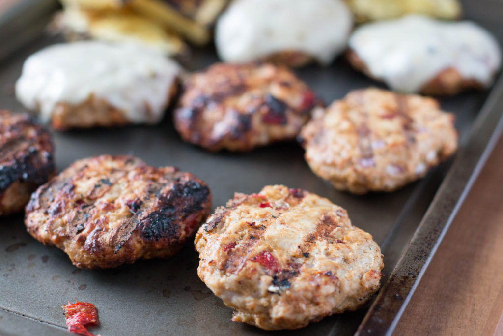 Close up picture of turkey burgers without buns. Some with cheese and some without cheese.