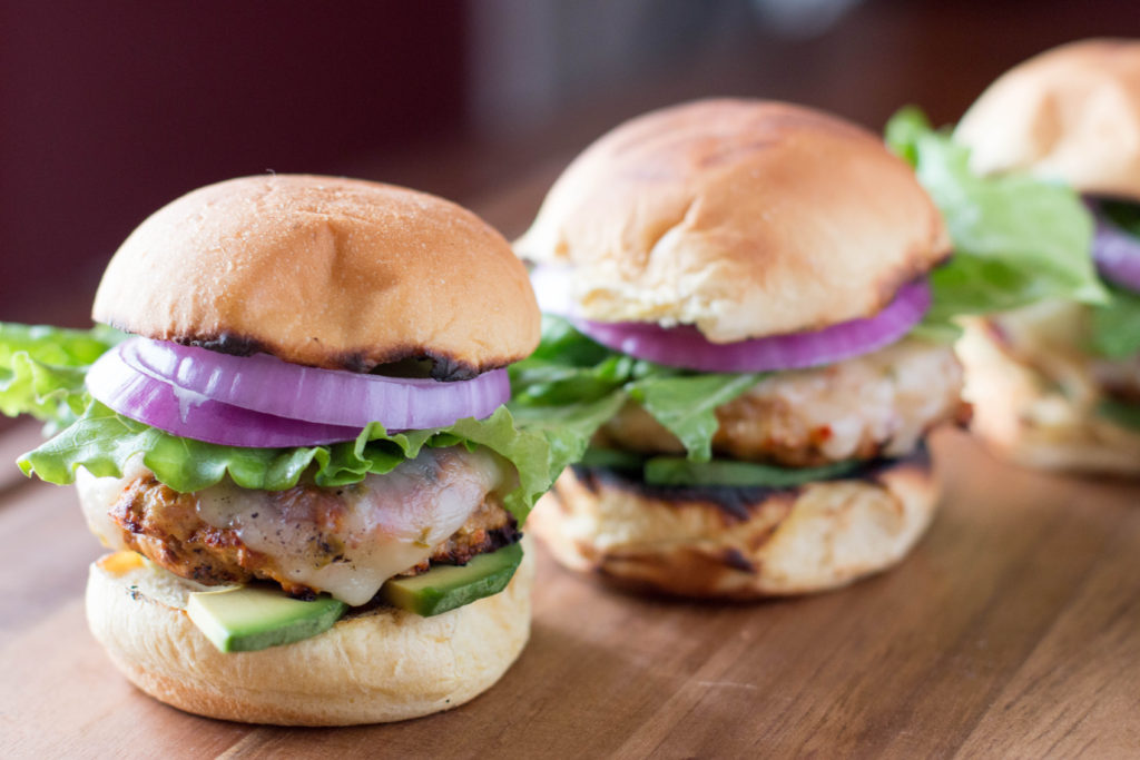 Picture of 3 grilled turkey burger sliders with toppings.