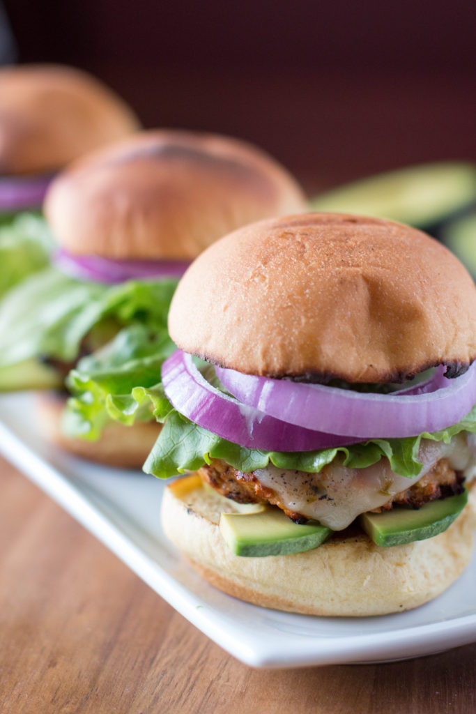 Close up picture of grilled turkey burger sliders with toppings