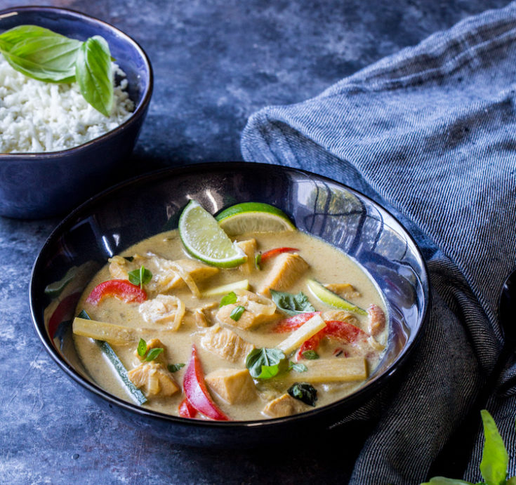 thai green curry with bell peppers and sliced limes with a bowl of cauliflower rice