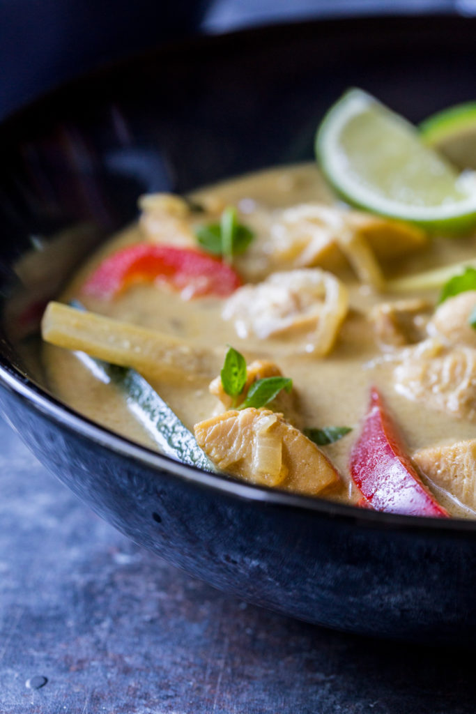 close up image of thai green curry with bell peppers and sliced limes