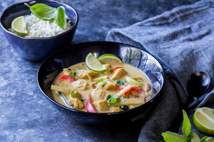 horizontal image of thai green curry with bell peppers and sliced limes
