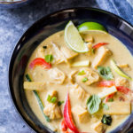 close up image of thai green curry with bell peppers and sliced limes with cauliflower rice