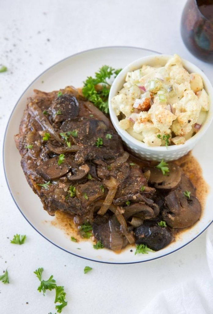 Crock pot pork chops with cooked mushrooms and a brown sauce on top on a white plate with a blue rim and a white bowl of what looks like potato salad also on plate