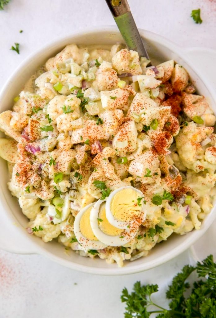 cauliflower potato salad with sliced hard boiled eggs and paprika on top in a white bowl with the tip of a spoon coming out of the potato salad