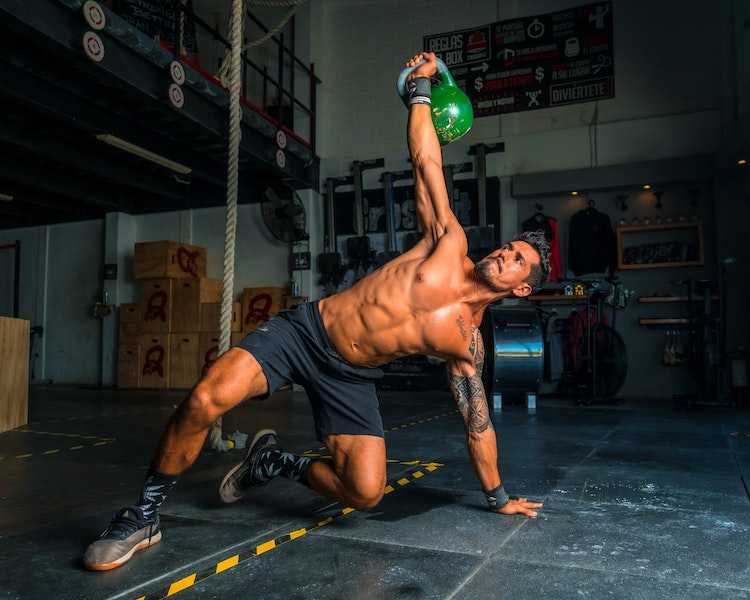 athletic man lifting a green kettle bell
