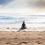woman meditating at the ocean